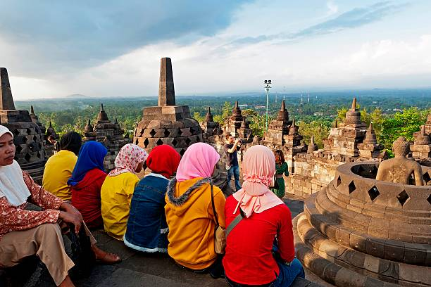Indonesia. Java. Borobudur. A group of very colourfully dressed. seated Muslim women look out over the monument to the surrounding countryside. (Photo by: David Cumming/Eye Ubiquitous/UIG via Getty Images)